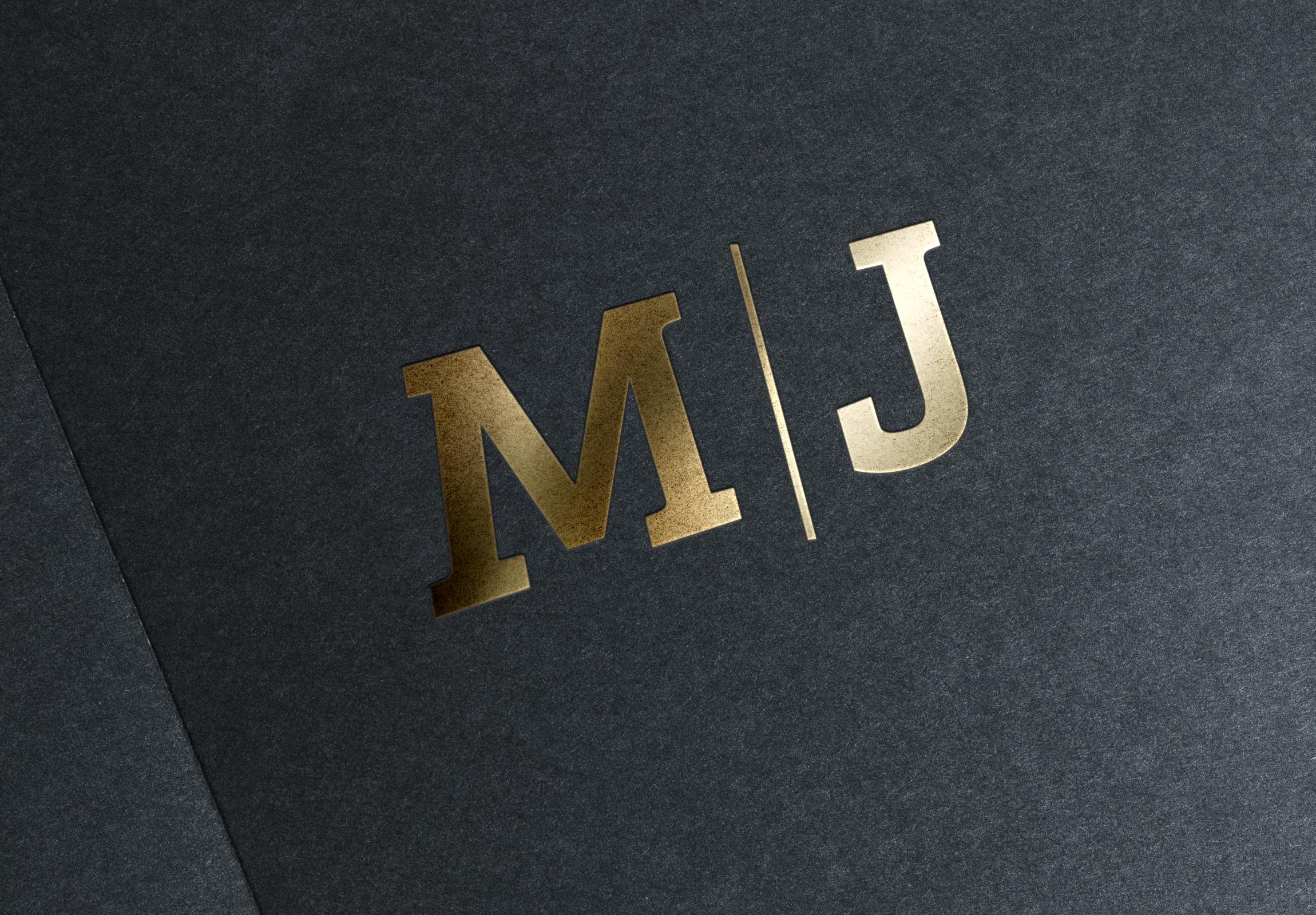 M/J gold logo on black paper