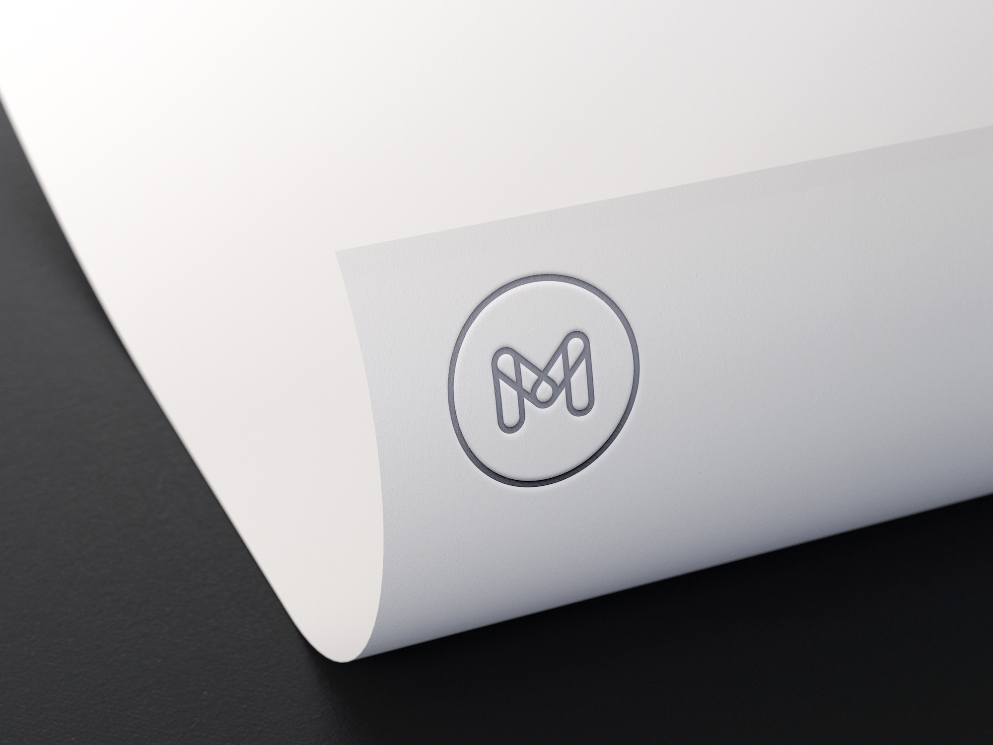M silver logo on white paper